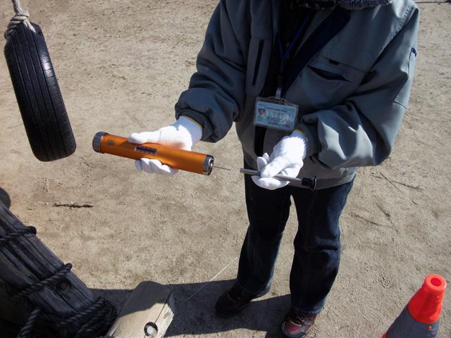 木製遊具腐食測定機の針を専用工具で押し込む。